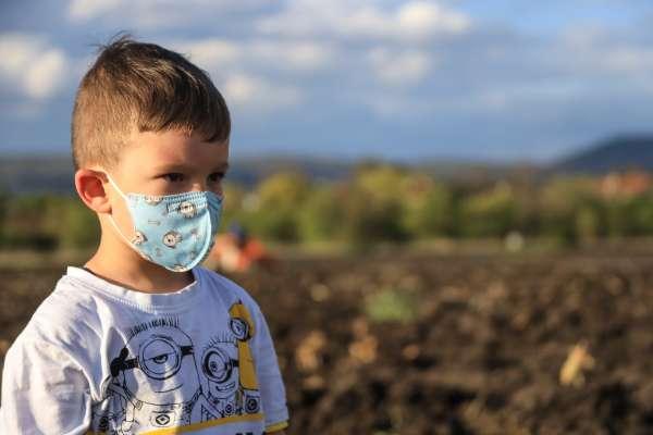 Little boy standing in field wearing a blue face mask