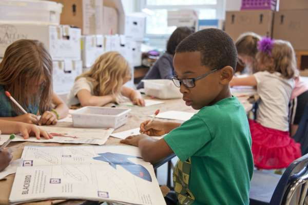 Kids sitting at desk writing in notebook