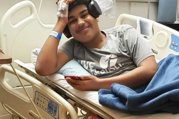 Max laying in hospital bed wearing headphone and smiling
