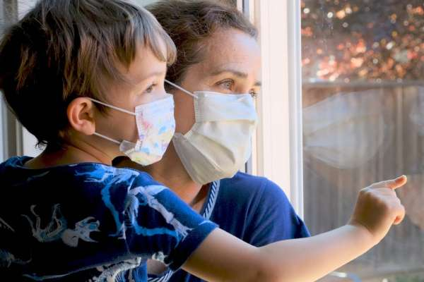 Woman and child wearing masks looking out window