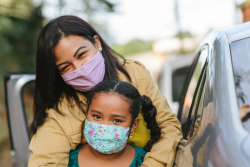 Woman holding a child while both wearing masks