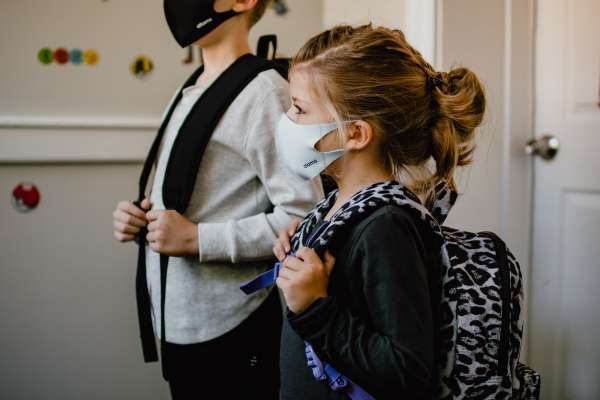 Little boy and girl wearing masks and carrying backpacks