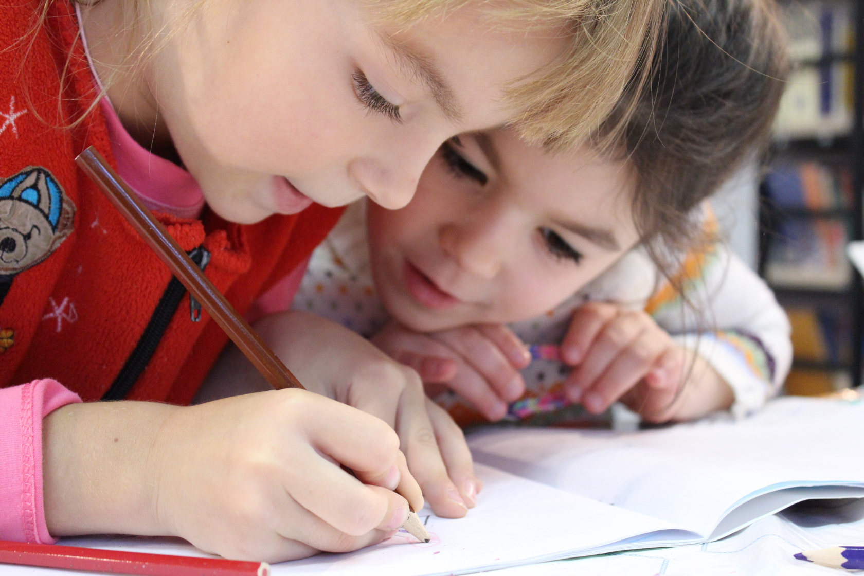 Two young girls drawing on paper