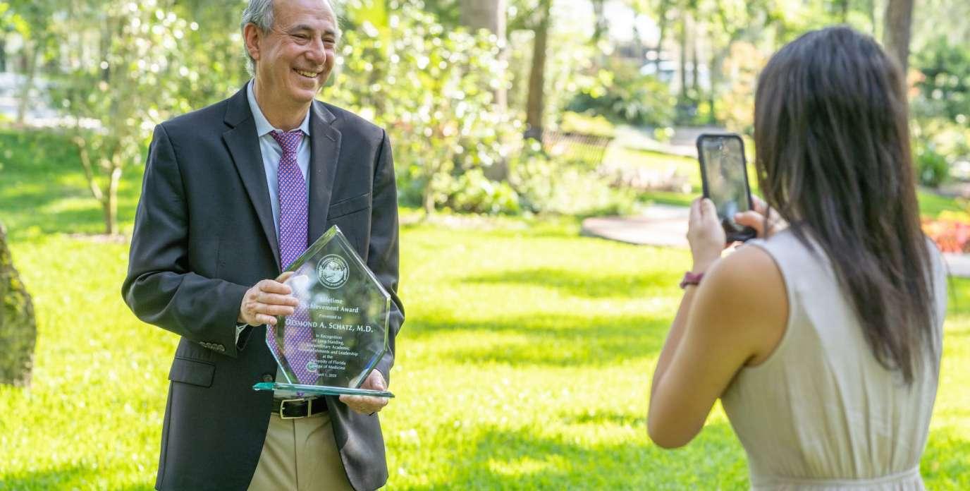 Dr. Schatz holding award