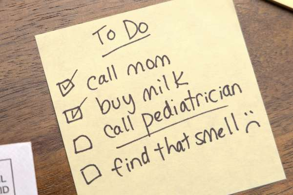 A yellow sticky note with lists: Call mom; buy milk; call pediatrician; find that smell.