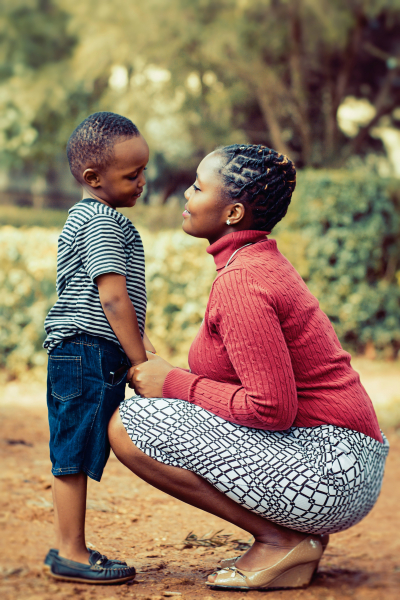 Woman kneeling down to talk to young boy