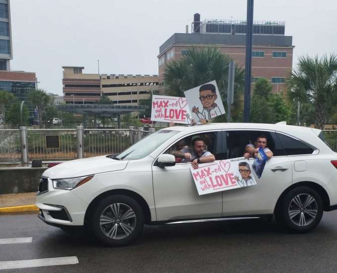People holding signs and waving from a white car