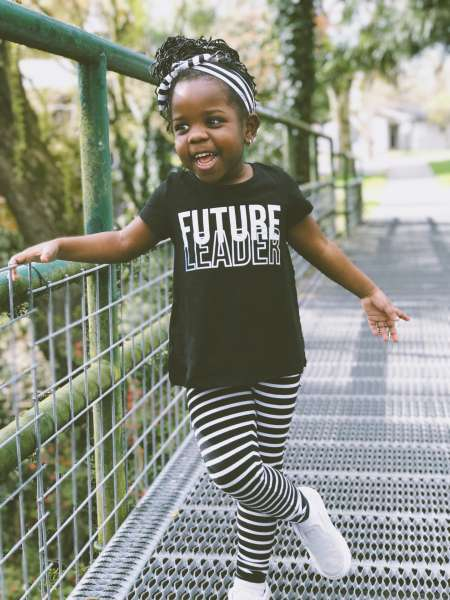 "Little girl giggling and wearing a shirt that reads ""Future Leader"""