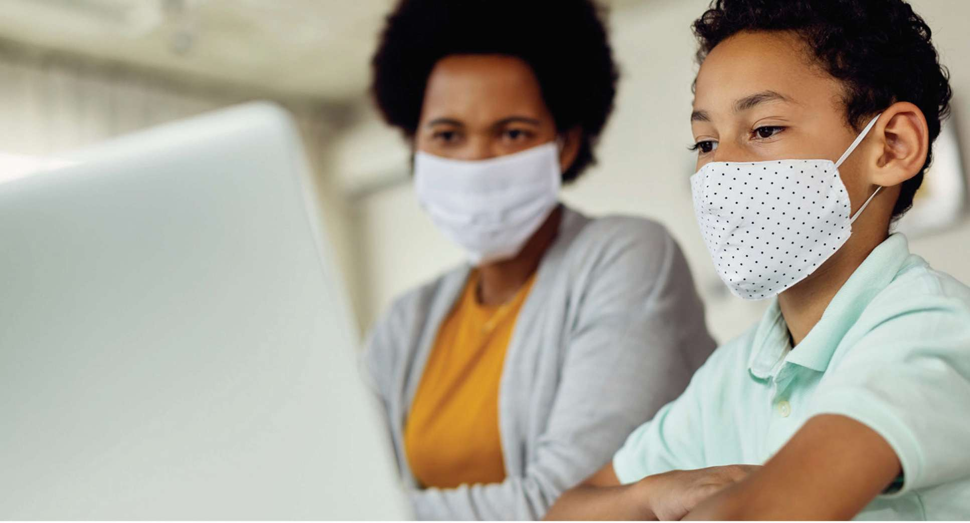 Child and parent wearing face masks and using a computer